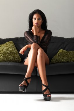Sexy leggy woman in heels on black leather sofa