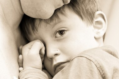 Nice image of a young upset boy cuddling his mum stock vector