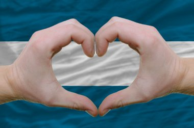 Heart and love gesture showed by hands over flag of el salvador
