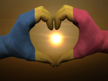 Heart and love gesture by hands colored in romania flag during b