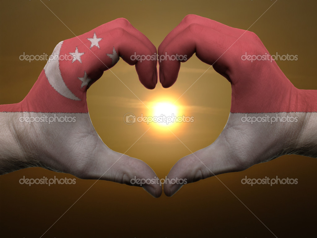 Heart and love gesture by hands colored in singapore flag during
