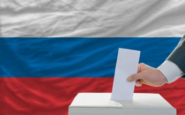Man voting on elections in russia in front of flag