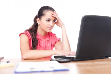 Beautiful young woman sitting at office desk and working on lapt