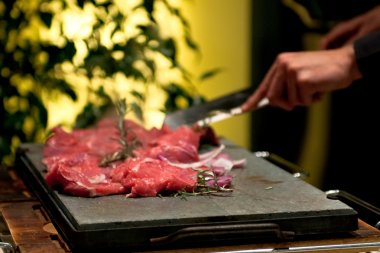Meat cooking on the stone plate at the restaurant