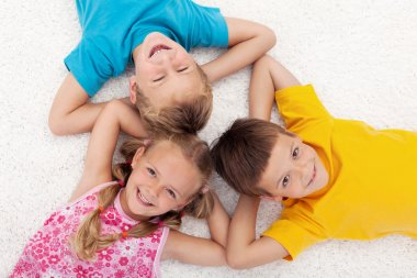 Three kids laying on the floor in circle