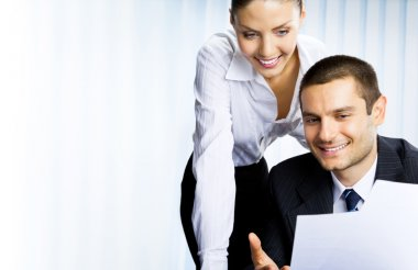 Two businesspeople working with document at office