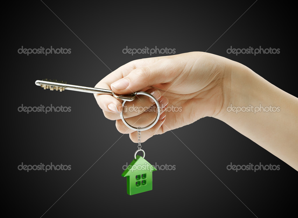 Hand holding key with a keychain in the shape of the house