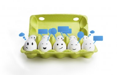 Group of happy smiling eggs with social chat sign and speech bubbles. Ten white eggs in a carton box representing a social network. On a white background stock vector