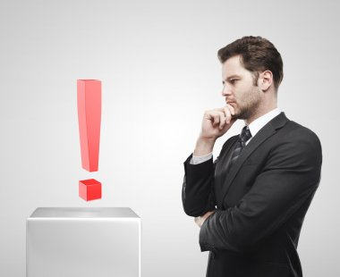 Young businessman look at the red exclamation mark on a white pedestal.