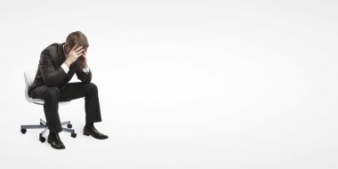 Young businessman sitting on chair with head down as if sad or depressed.