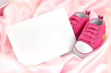 Pink baby booties and a blank card on pink silk stock vector