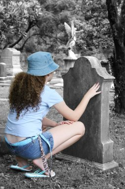 A young girl lookin at a tombstone in a graveyard stock vector