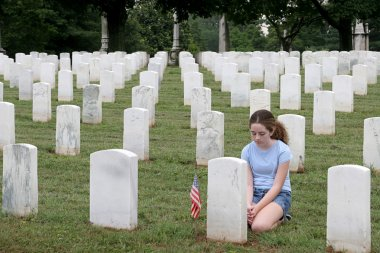 A young girl in a military cemetary honoring a fallen soldier stock vector