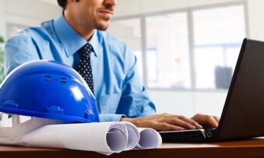Engineer using his laptop. Focus on blueprints. stock vector
