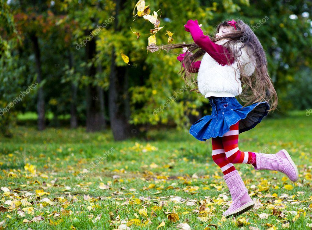 Cute little girl wearing fur coat in autumn forest