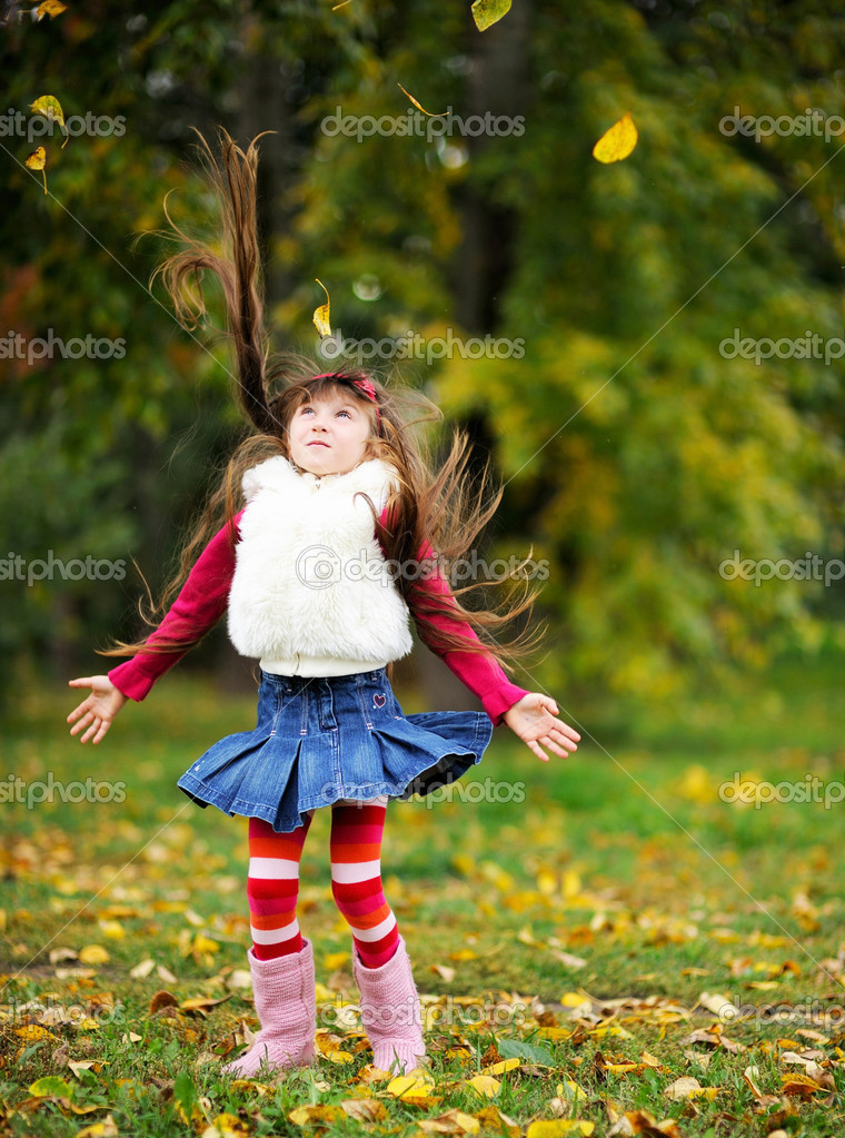Cute little girl wearing fur coat in autumn forest