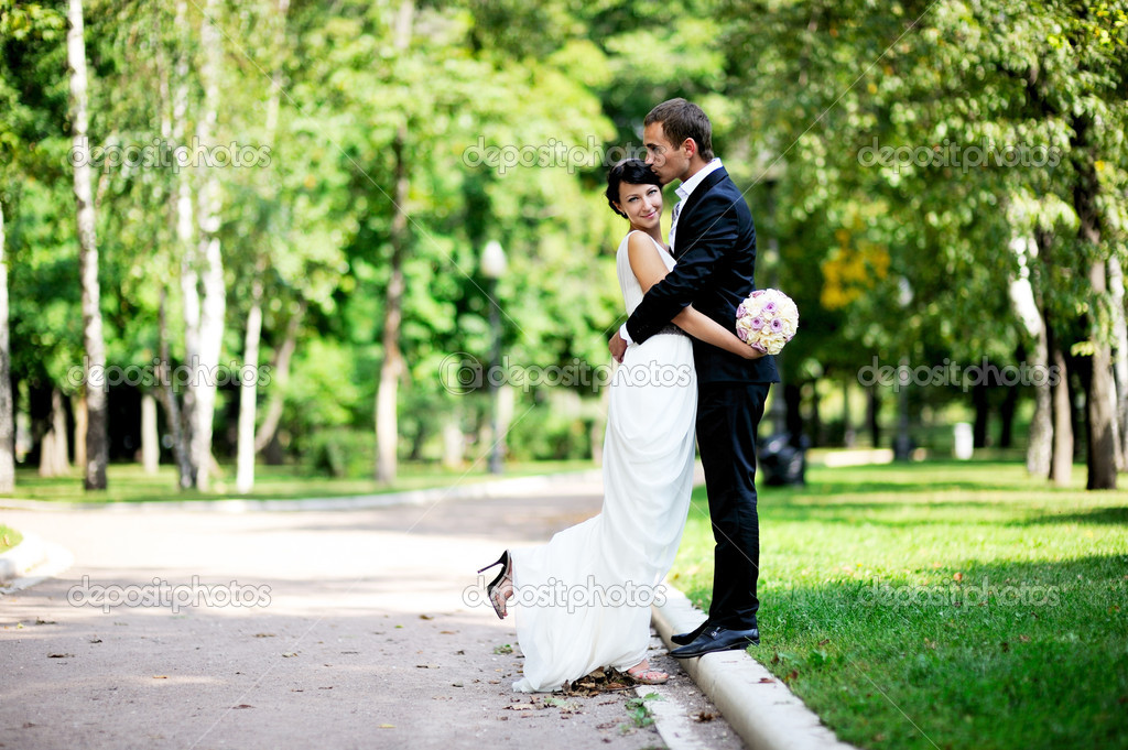 Bride and groom walking in a summer park
