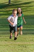 Fotografie zwei Kleinkinder laufen und spielen