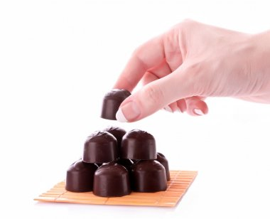 Hand take chocolate isolated on white