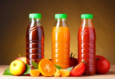 Different juices and fruits on wooden table on brown background