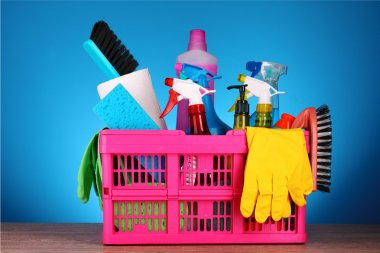 Cleaning supplies in basket on blue background