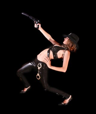 Beautiful woman aiming with gun on black background