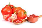 chutné kečup v dřevěnou lžící a rajče izolovaných na bílém