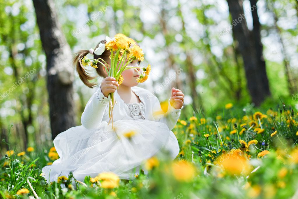 Cute girl in the park with dandelions