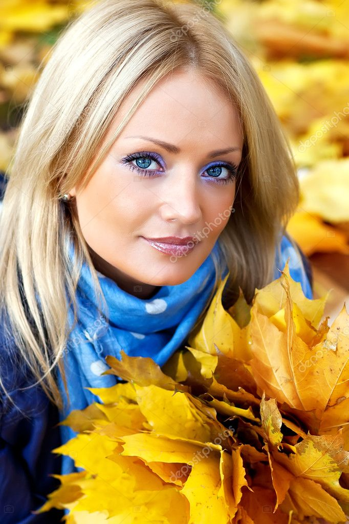 Cute blonde with a bouquet of autumn leaves