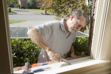 Carpenter repairing window frame