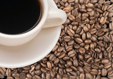 Freshly brewed coffee in white cup over dark roasted coffee bean