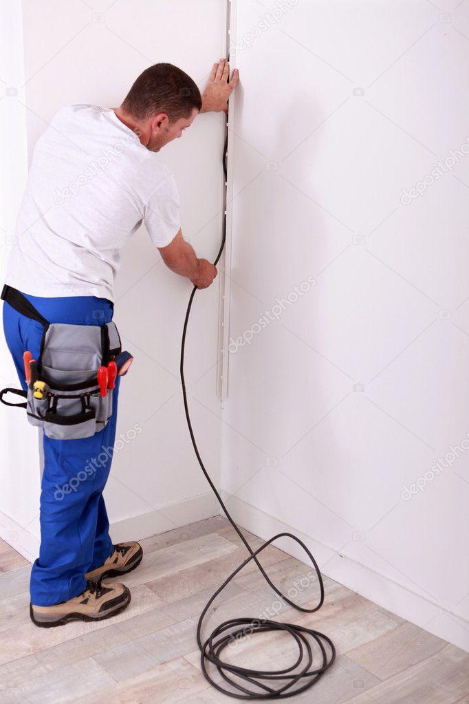 Elektriker einen Draht an einer Wand Befestigung — Stockfoto ...
