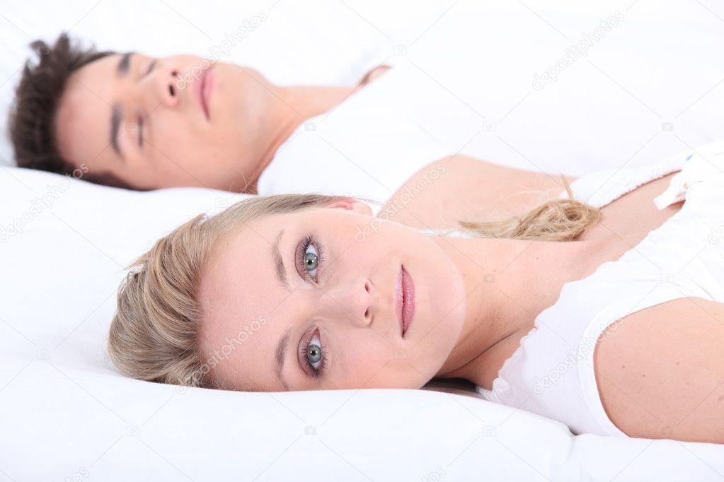 Mann und Frau mit offenen Augen im Bett - Stockfotografie