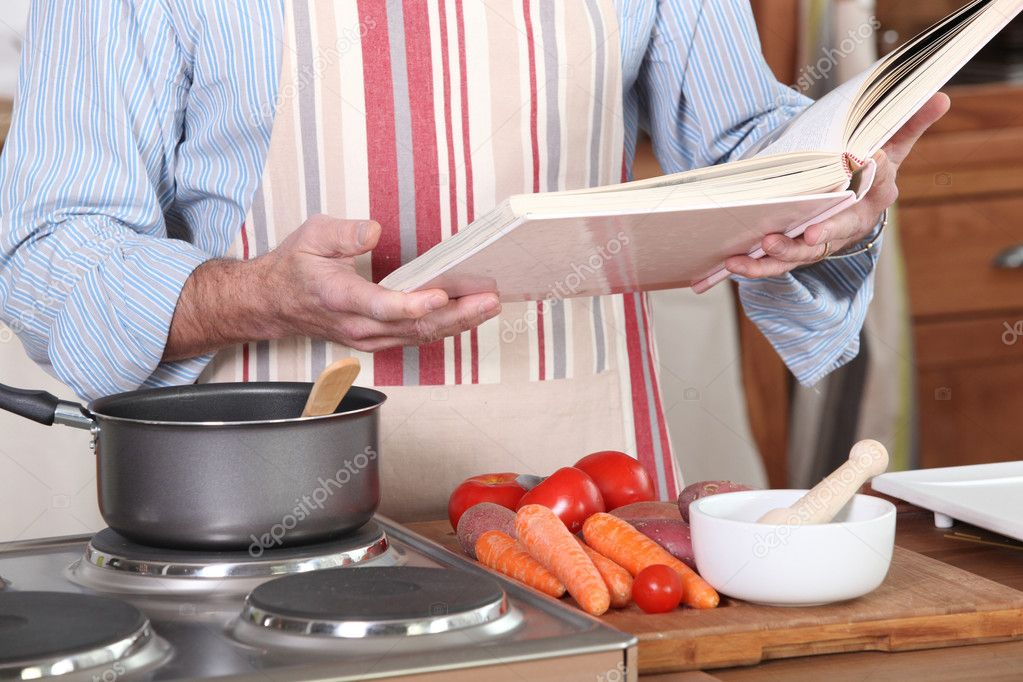 A man reading a recipe book in his kitchen stock photo a man reading a recipe book in his kitchen photo by photography33 forumfinder Image collections