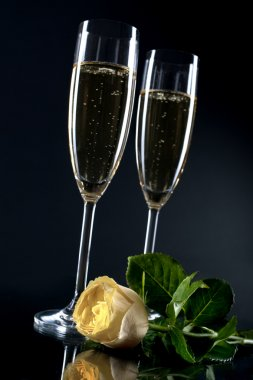 Two champagne flutes with a rose