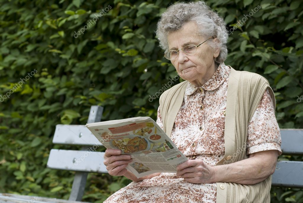 Old woman reading newspaper — Stock Photo © alexraths #6870476