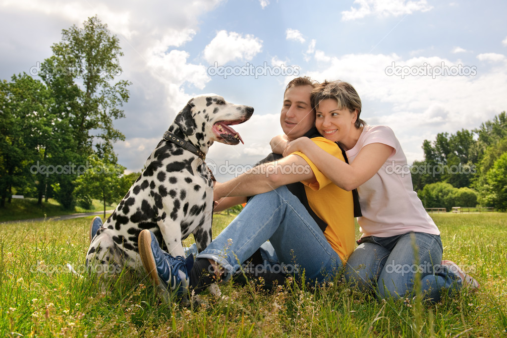 Loving couple with a Dalmatian outdoors