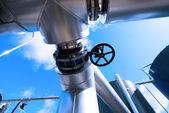 Průmyslová zóna, ocelové potrubí a ventily proti modré obloze