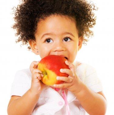 Pretty little girl biting an apple
