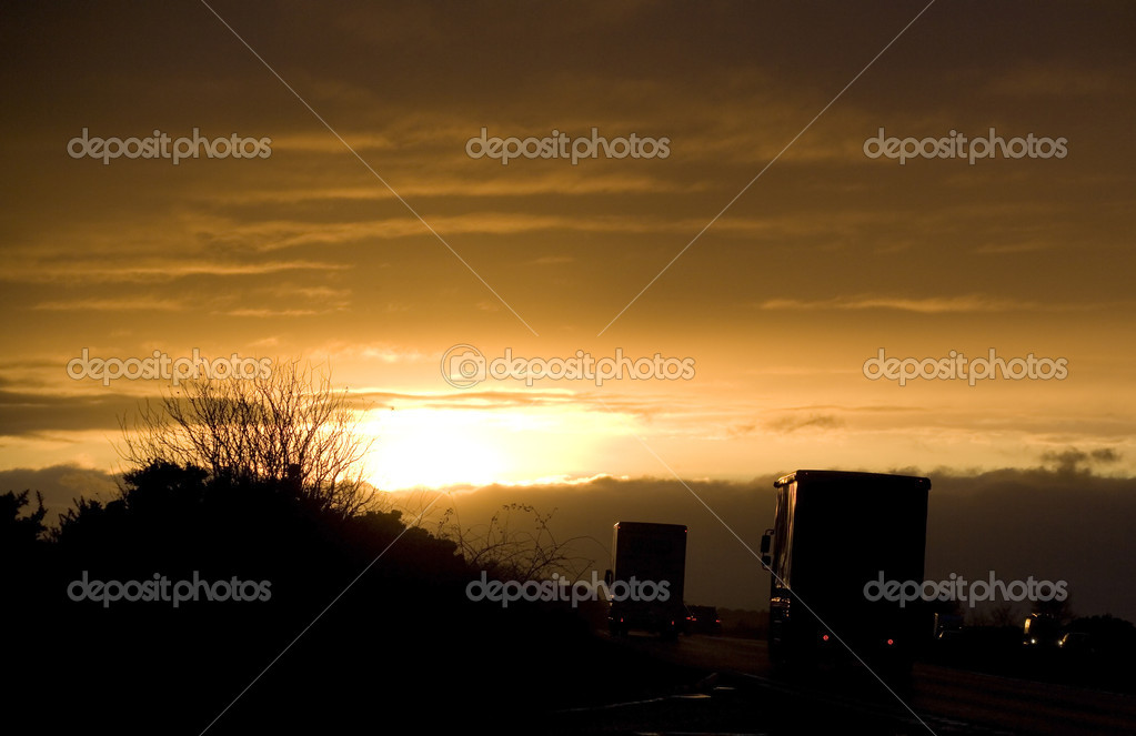 Lorries on a road at sunset