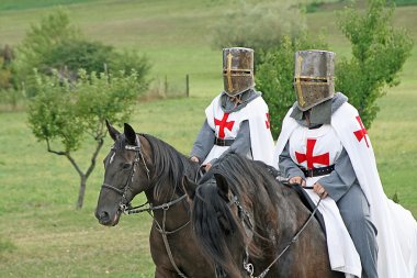Two medieval crusaders shall strutting with their horses blacks in the Ital