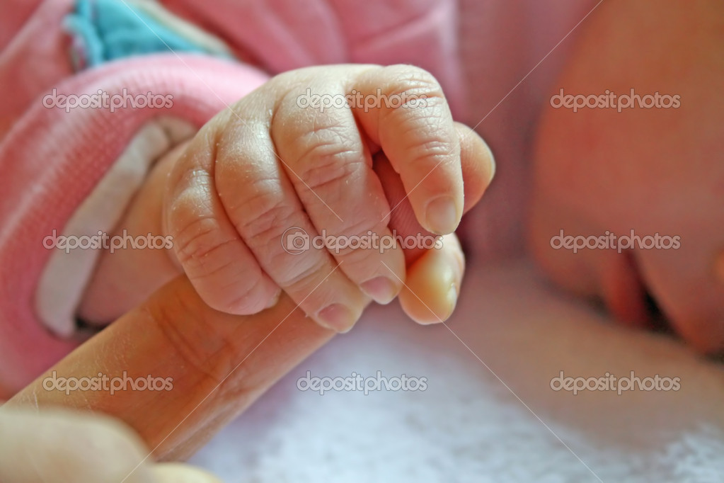 Baby shakes hands with his finger to his father