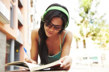 Cute girl listening music and studying