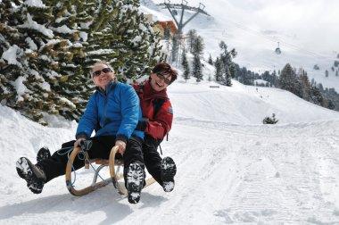 Senior couple on sledge having fun