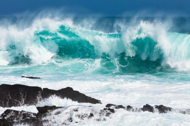 Turquoise rolling wave slaming on the rocks