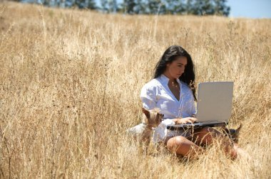 Beautiful woman working on a laptop in the middle of a field
