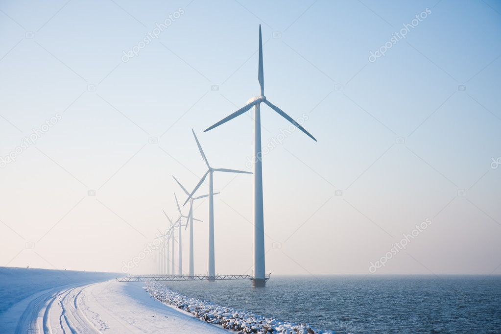 Row of snowy windmills standing in Dutch sea disappearing in win