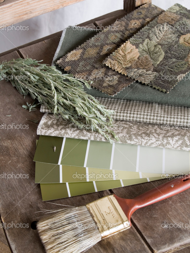 Earthy green tone paint sample cards, fabric swatches and a paintbrush on a rustic, unpainted chair with a twig of sagebrush.