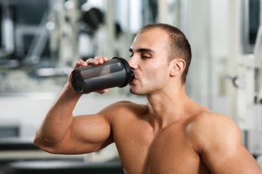 Bodybuilder in the gym, drinking a protein shake stock vector
