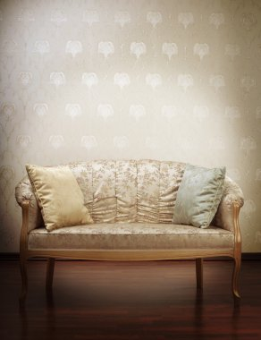 Luxury gold glamorous sofa in the background of vintage wallpape
